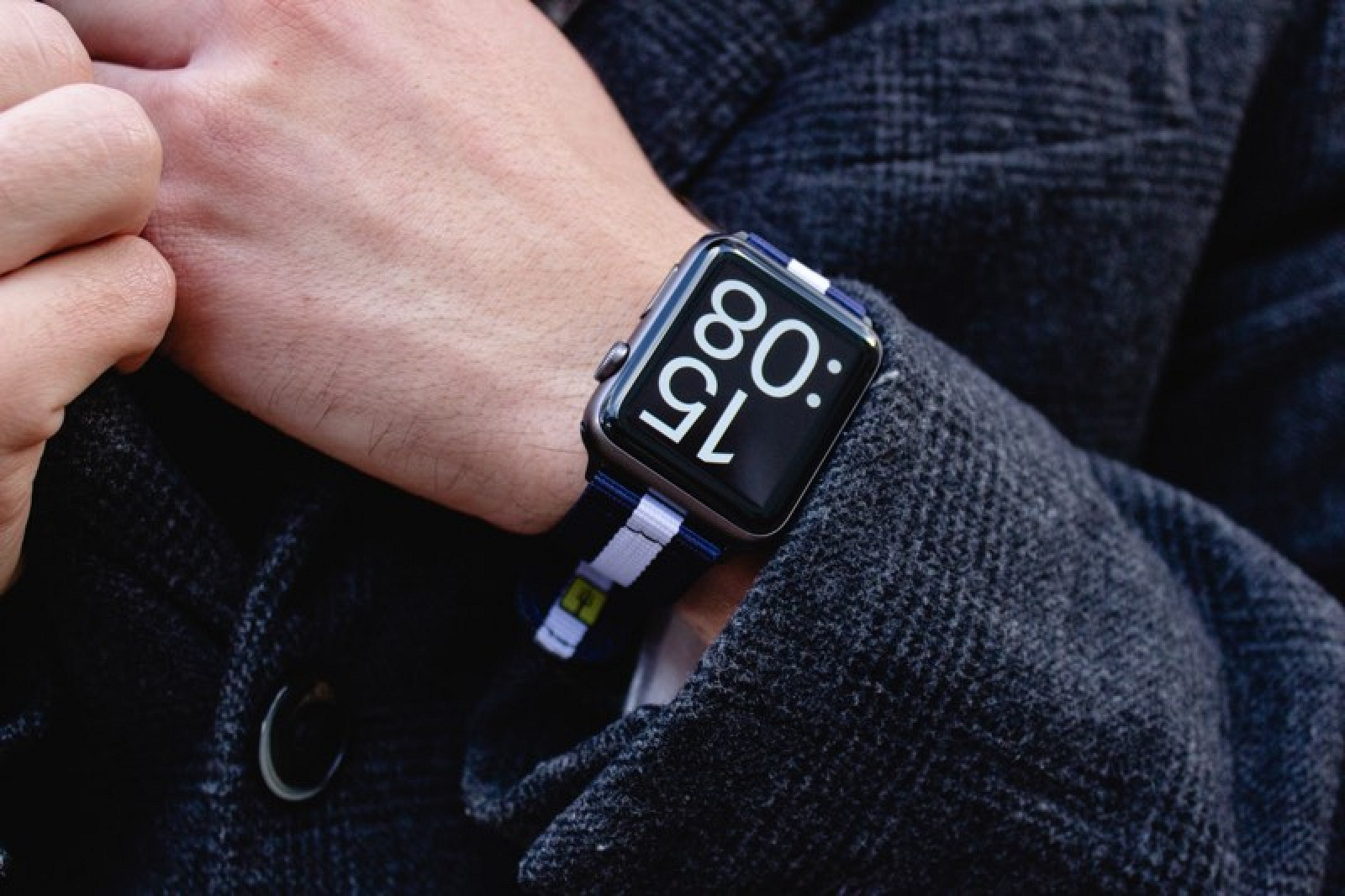 Apple watch showing 15:08 worn by a person wearing a patterned sweater.