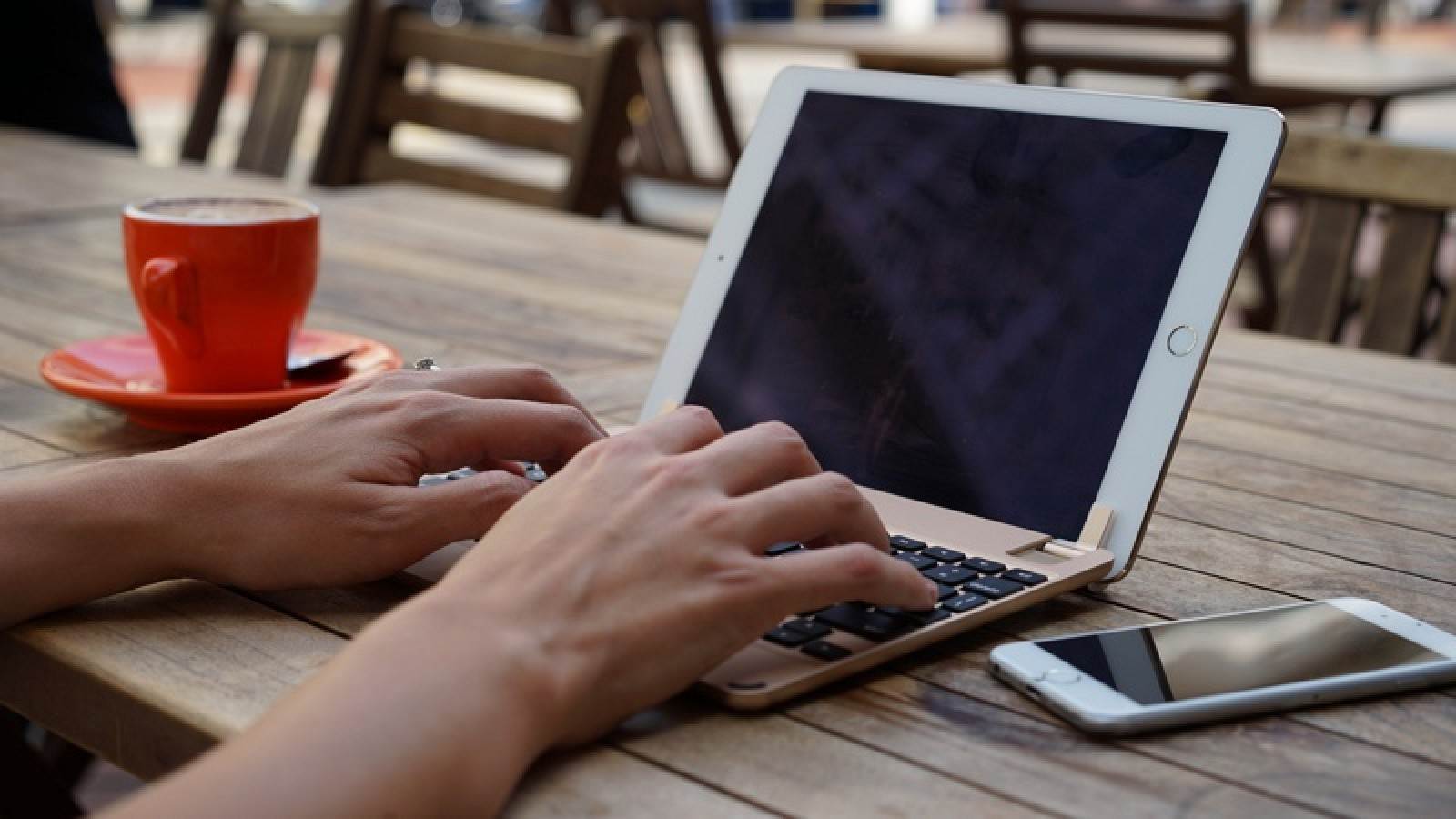 A hand is encoding on iPad using an installed keyboard. The iPad is beside a white iPhone 6s on the right and an orange cup on the left side. These items are set on an brown wooden table.
